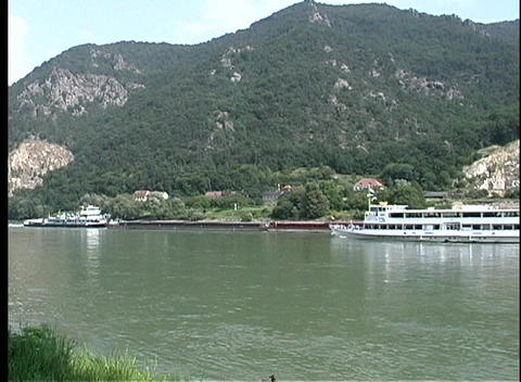 A cruise boat travels along the beautiful Danube River Footage