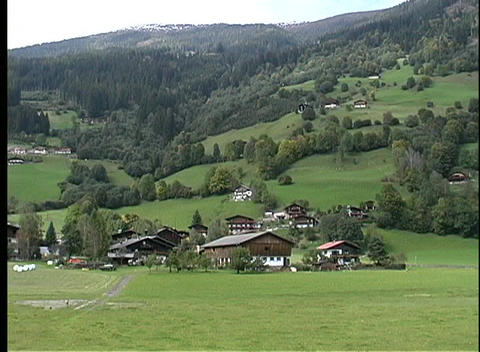 Shadows of clouds flow over a small community in the rolling hills of Austria Footage