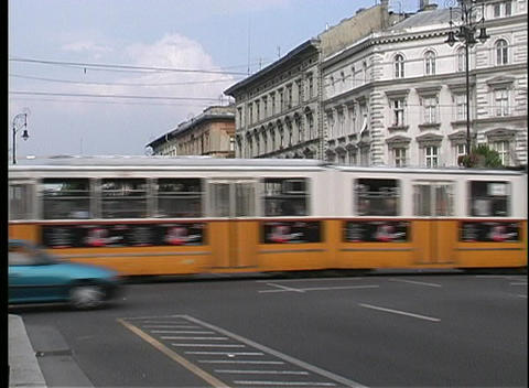 Traffic, trolleys, and trams drive past old buildings in... Stock Video Footage