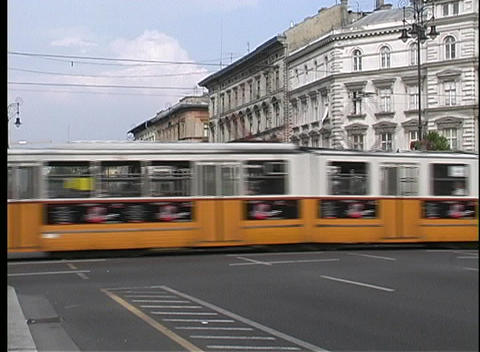 Traffic, trolleys, and trams drive past old buildings in Budapest Footage