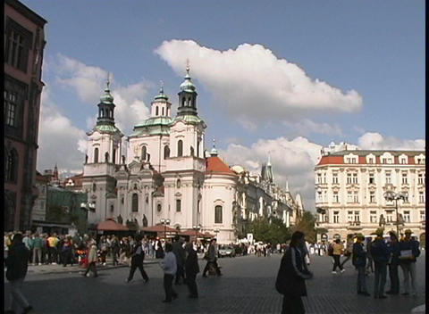 A medium-shot of the Church of St. Nicholas, Prague, and in the foreground, people walking on the st Footage