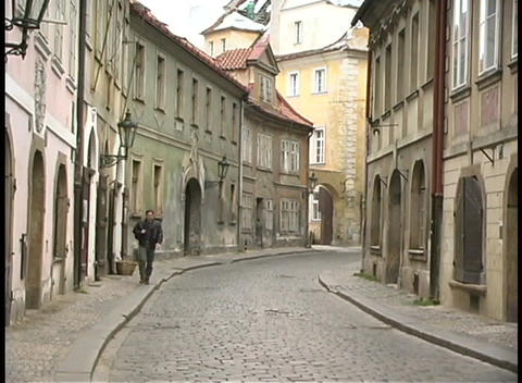 A medium shot of a man walking along a cobblestone street... Stock Video Footage