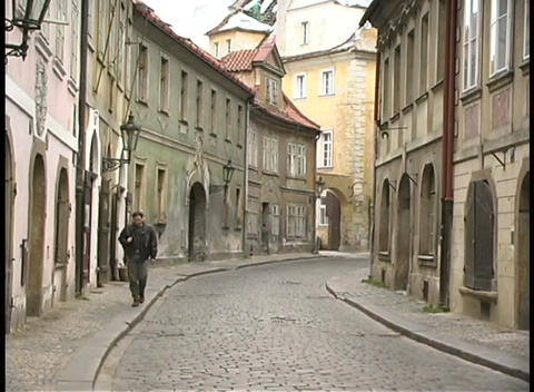 A medium shot of a man walking along a cobblestone street in Prague Footage