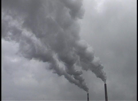smokestacks with dark, grey smoke billowing out of the tops Footage