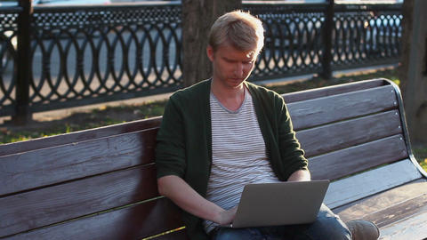 Man in park working laptop reading and writing messages browsing Footage