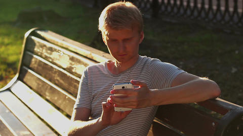 Young blond adult man writing sms message in park bench sitting Footage