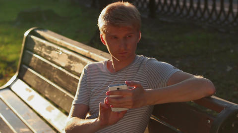 Blond male writing sms message to girlfriend sitting in park Live Action