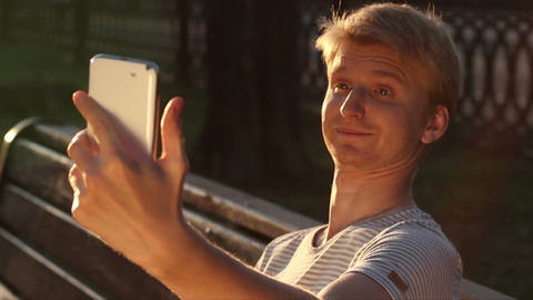 Funny blond man taking photo himself in park for social networks Footage