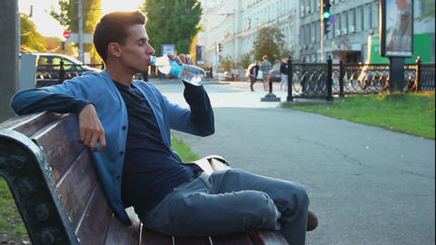 Young adult male sitting in park enjoying life drinking water Footage