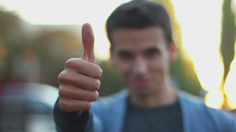 Young man thumb up right hand rack focus, daytime outdoors park Footage