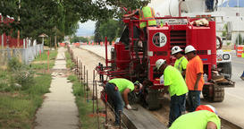 Construction workers new concrete curb gutter DCI 4K Footage