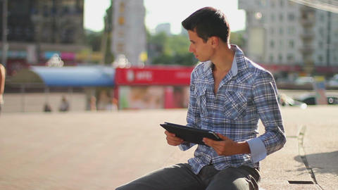 Young business man reading tablet pc computer on city square Footage