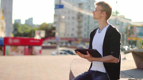 Young male with tablet pc pad smiles reads device on city square Footage