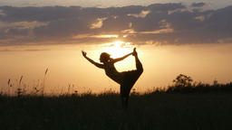 Young woman silhouette entering dancer yoga pose in front of beautiful sunset, F Footage