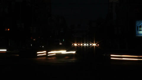 Dark time lapse of city cross road, yellow car lights visible Footage