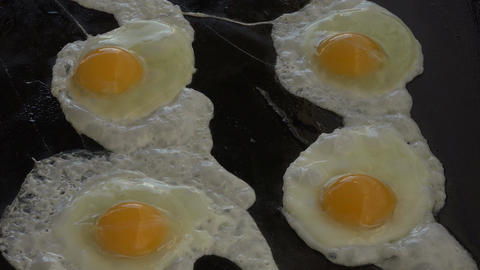 Eggs being cooked on iron grill for breakfast 4K 083 Footage