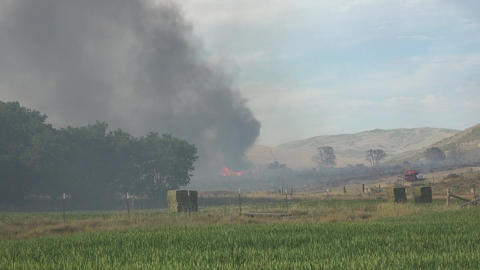 Farm building destroyed by wildfire fireman watch fast 4K 004 Footage