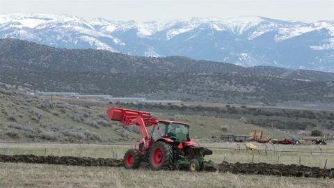 Farmer in heavy duty tractor plow field HD 2448 Footage