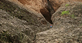 Father climbing steep mountain cliff to cave DCI 4K Footage