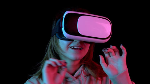 Young woman in VR glasses closeup. A woman immersed in virtual reality makes Live Action