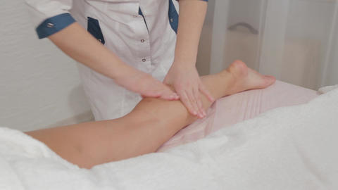 Woman massage therapist does massage on the legs of a young girl Live Action