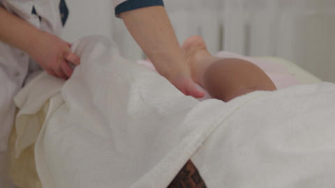 Woman massage therapist covers girl legs with a towel Live Action