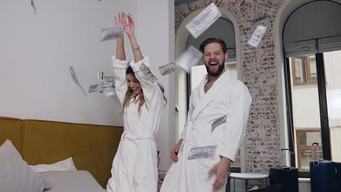 Slow motion of cheerful attractive amorated couple in bathrobes which scattering Live Action