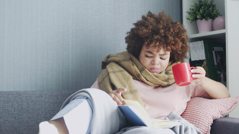 A woman has a cold at home. Lying on the couch with a book and cup of a hot tea Live Action