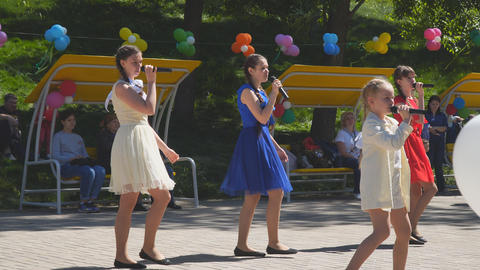 Performance of girls in the park on holiday. Girls sing in the park Live Action