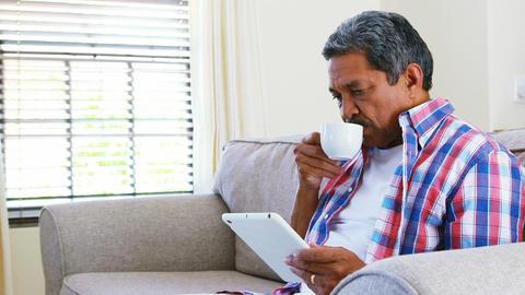 Senior man using digital tablet while having coffee in living room 4k Live Action