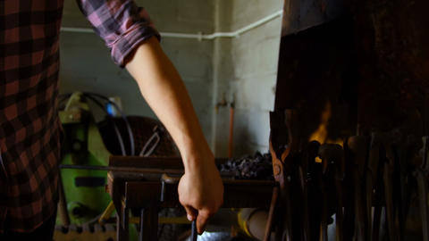 Female metalsmith heating horseshoe in fire 4k Live Action