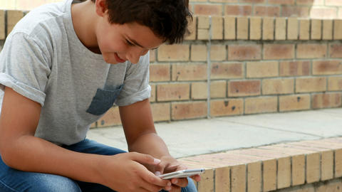 Happy schoolboy using mobile phone Live Action