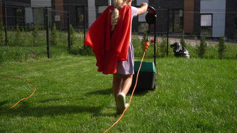 Super girl girl in red cloak mowing lawn in fenced house yard. Corded lawn mower Live Action