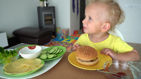 White european kid eating tasty big burger with great appetite. Gimbal motion Live Action