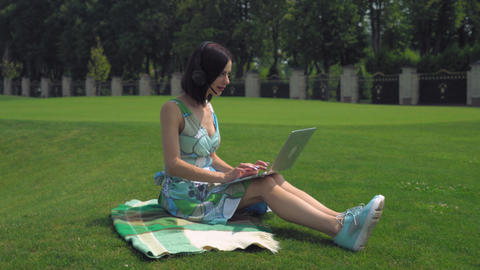 A young girl sits on blanket and typing on a laptop outdoors Footage