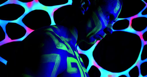 Profile shot of a man with green bright body art all over his body, uv light, 4k Live Action