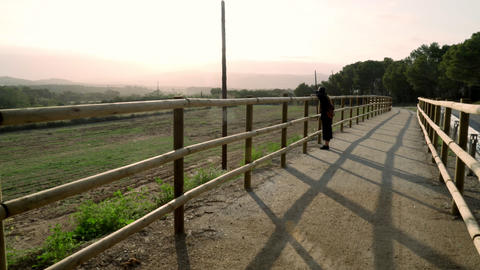 Girl with long hair in black kaftan dress and black hat leans on a fence on a Live Action