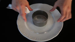The cook puts the dessert ring on a clean plate.Cooking Ring.Food Ring.Close-up Live Action