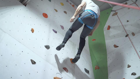 Sporty young man climbing indoors with belay, descending from top Live Action