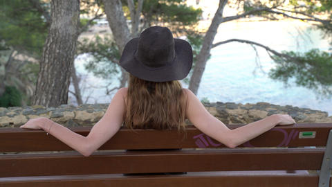Girl with long hair in black silk dress and black hat sitting on the bench on Live Action