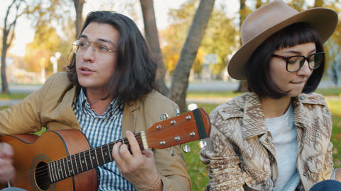 Portrait of creative youth singing playing the guitar relaxing in urban park Live Action