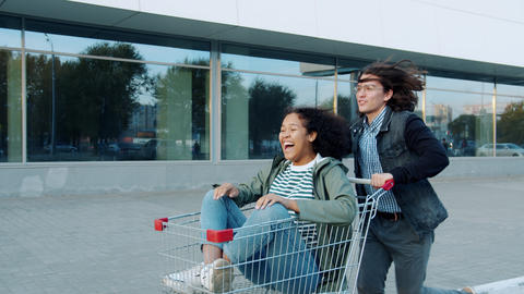 Playful youth girl and guy having fun outdoors riding shopping cart laughing Live Action