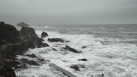Beautiful waves hit the rocks. Cloudy weather. Swaying sea. Romantic view of the Live Action