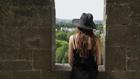Girl with long hair in black silk dress and black hat stands on the castle Live Action