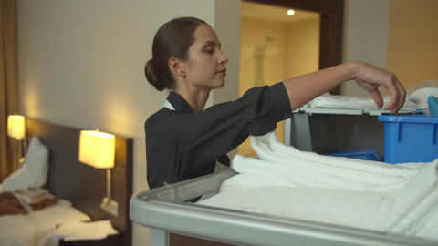 Young housemaid take towels and cleaning equipment Live Action