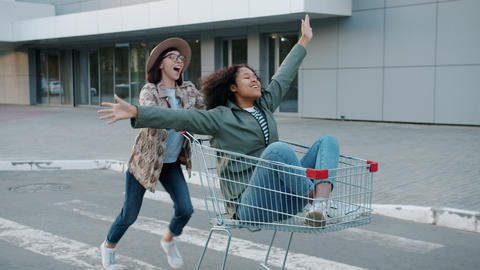 Playful young ladies friends having fun outside riding shopping cart in street Live Action