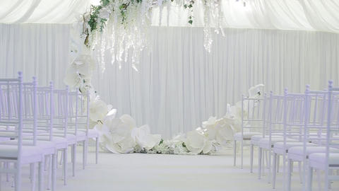 Large spacious white wedding room with a large wedding cute wreath, under which Live Action