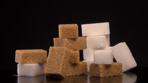 Cubes of brown and white sugar rotating on white background Live Action
