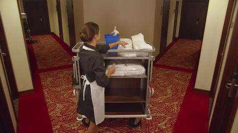 Housemaid take towels and cleaning equipment in corridor of hotel Live Action