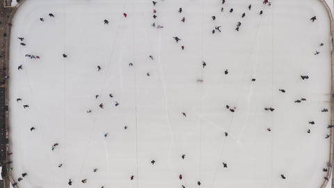 Top view of a winter ice rink and people skating in slow motion. Winter rink in Live Action